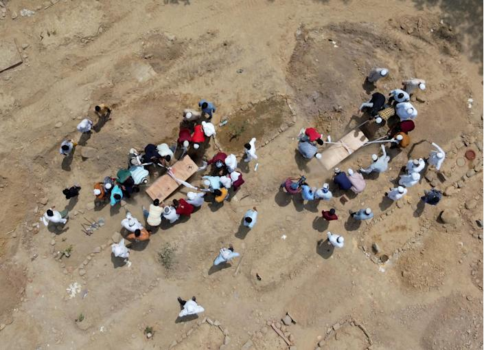 """People bury the bodies of COVID-19 victims at a graveyard in New Delhi on April 16, 2021.<span class=""""copyright"""">Danish Siddiqui—Reuters</span>"""