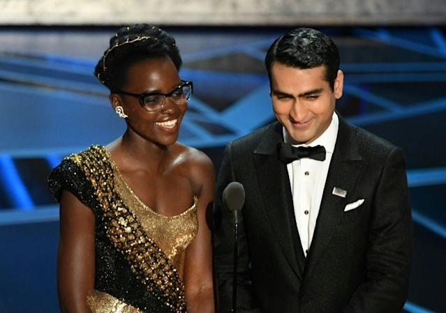 <p>Lupita Nyong'o wears cat-eye glasses with her custom Versace gown while presenting with Kumail Nanjiani at the 2018 Oscars. (Photo: Getty Images) </p>