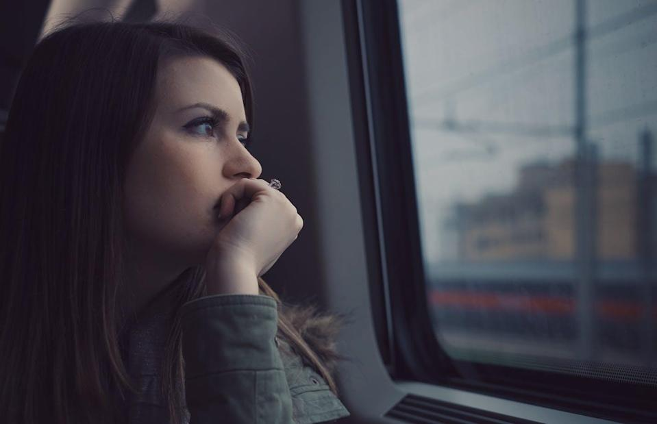 A woman gazes out of a commuter vehicle window.