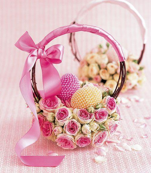 <p>Tightly packed blossoms form the base of this basket. To make, place soaked floral foam on a teacup saucer and insert rose stems to create the base. Then insert dried grapevines to form a handle and decorate with a satin ribbon. Fill it with bejeweled eggs for a luxe look. </p>