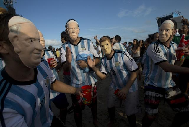 "FILE - In this Wednesday, July 9, 2014 file photo, soccer fans of the Argentina national soccer team wear masks with faces of Pope Francis and Argentine soccer player Lionel Messi during a live telecast of the soccer World Cup semifinal match between Argentina and Netherlands, inside the FIFA Fan Fest area on Copacabana beach, in Rio de Janeiro, Brazil. The Vatican says it is unlikely that Pope Francis and his predecessor, Pope Emeritus Benedict XVI, would get together to watch their home teams in the World Cup final on Sunday. Vatican spokesman, the Rev. Federico Lombardi, said Thursday, July 10, 2014 that the hour of the final is late for Francis' routine, and acknowledged with a chuckle that Benedict wasn't known as an avid sports fan. Still, he didn't rule anything out, saying, ""we'll see in the coming days."" Pope Francis has already given his word that there would be no papal intervention in Argentina's fortunes, promising he wouldn't pray for any team. German-born Benedict's inte"