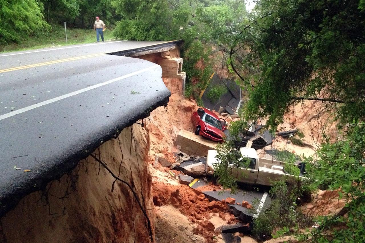 Vehicles rest at the bottom of a ravine after the Scenic Highway collapsed near Pensacola, Fla., Wednesday April 30, 2014. Heavy rains and flooding have left people stranded in houses and cars in the Florida Panhandle and along the Alabama coast. According to the National Weather Service, an estimated 15-20 inches of rain has fallen in Pensacola in the past 24 hours. (AP Photo/Pensacola News Journal, Katie E. King)