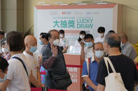 In this Tuesday, June 15, 2021, photo, people wearing face masks to help prevent the spread of the coronavirus, line up to register for a coronavirus vaccine incentive lottery in a Grand Central residential building complex in Hong Kong. Coronavirus vaccine incentives offered by Hong Kong companies, including a lucky draw for an apartment, a Tesla car and even gold bars, are helping boost the city's sluggish inoculation rate. (AP Photo/Kin Cheung)