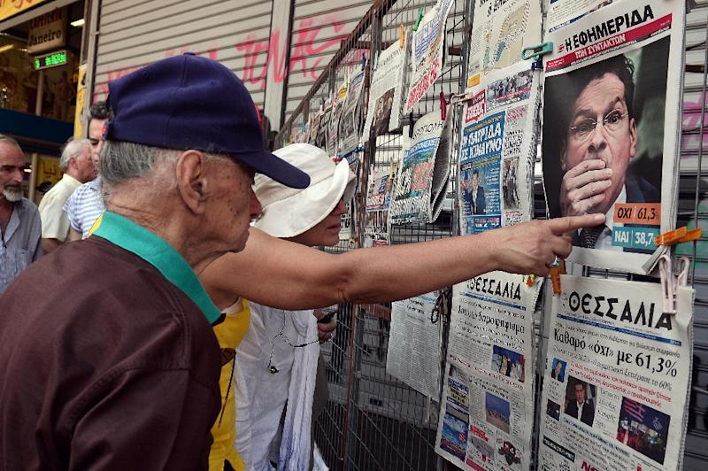 People read newspapers' headlines showing the results of Greece's referendum, in Athens, on July 6, 2015 (AFP Photo/Louisa Gouliamaki)