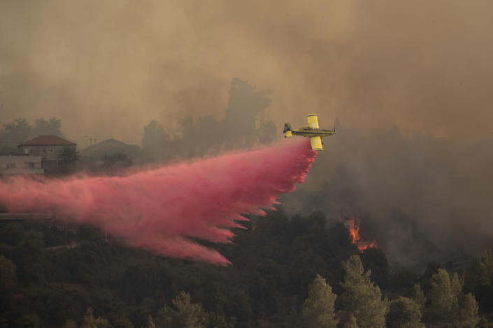 A plane sprays wildfires burning for for the second day near Shoresh, on the outskirts of Jerusalem, Monday, Aug. 16, 2021. Israel Fire and Rescue service said in a statement that 45 firefighting teams accompanied by eight planes were working to contain five fires in the forested hills west of the city. (AP Photo/Maya Alleruzzo)