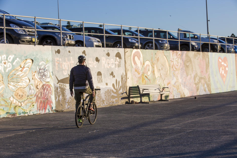 A man cycles in front of a wall covered in graffiti at the south end of Bondi Beach.
