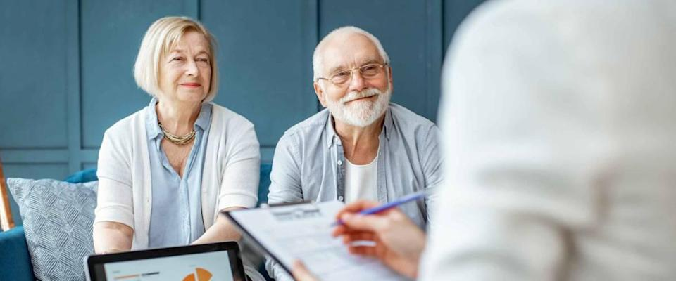 Happy senior couple during the meeting with agent or financial consultant.
