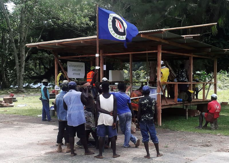 FILE PHOTO: Residents hold a Bougainville flag at a polling station during a non-binding independence referendum in Arawa