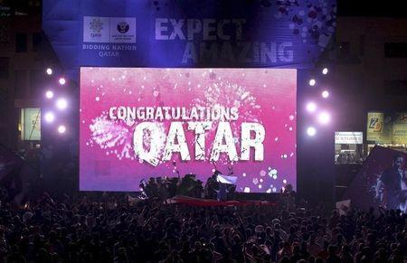 """People celebrate in front of a screen that reads """"Congratulations Qatar"""" after FIFA announced that Qatar will be host of the 2022 World Cup in Souq Waqif in Doha, December 2, 2010. REUTERS/Fadi Al-Assaad/Files"""