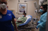 COVID-19 patient Daniel Wetherington, center, lies in a bed while being treated by nurses in an emergency room at Mission Hospital in Mission Viejo, Calif., Monday, Dec. 21, 2020. (AP Photo/Jae C. Hong)