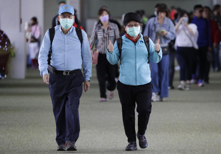 A passenger wearing a mask gestures as they arrive at Manila's international airport, Philippines, Thursday, Jan. 23, 2020. The government is closely monitoring arrival of passengers as a new coronavirus outbreak in Wuhan, China has infected hundreds and caused deaths in that area. (AP Photo/Aaron Favila)