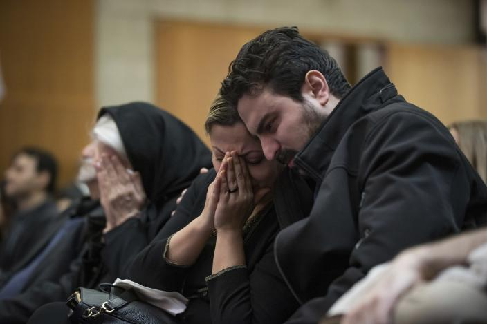 FILE - In this Jan. 19, 2020 file photo, Babak Razzaghi, right, consoles his sister Banafsheh Razzaghi as they mourn the loss of their sister Niloofar Razzaghi, brother-in-law Ardalan Hamidi and nephew Kamyar Hamidi, who died in a Ukraine airplane crash in Iran on Jan. 8, 2020, during a vigil, at the Har El synagogue in West Vancouver, British Columbia. More questions than answers remain about the disaster that killed 176 people on board the Ukrainian jetliner, a year after Iran's military mistakenly downed the plane with surface-to-air missiles. Officials in Canada, which was home to many of the passengers on the doomed plane, and other affected countries have raised concerns about the lack of transparency and accountability in Iran's investigation of its own military. (Darryl Dyck/The Canadian Press via AP, File)