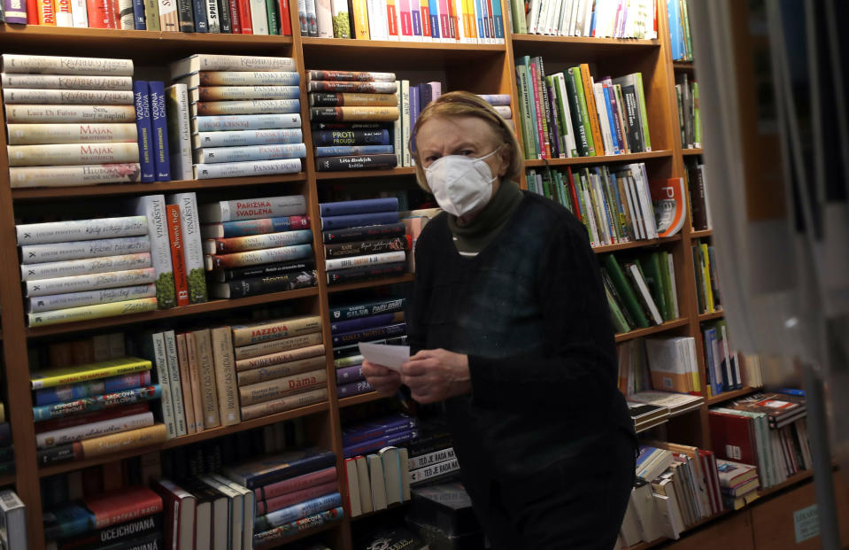 Marie Vytopilova, wife of the late Jaromir Vytopil, walks in a bookstore in Pelhrimov, Czech Republic, Thursday, Nov. 26, 2020. Some 25,000 have been killed by COVID-19 in the hard-hit Czech Republic. Jaromir Vytopil was one of them. His everyday presence in the small Czech town of Pelhrimov was something everybody took for granted for seven decades as he had served the generations of readers. The longest serving Czech bookseller, passed away on Nov 9. 2020, at age of 83. (AP Photo/Petr David Josek)