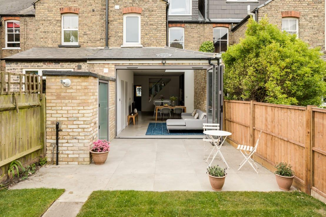 """<p>We kick off at the back of the house, where the new extension welcomes us in with its generous folding doors (when opened, that is), beautifully separating a stone-tile terrace from an open-plan<a rel=""""nofollow"""" href=""""https://www.homify.co.uk/rooms/kitchen"""">kitchen</a>, living area and dining spot.</p>  Credits: homify / Model Projects Ltd"""