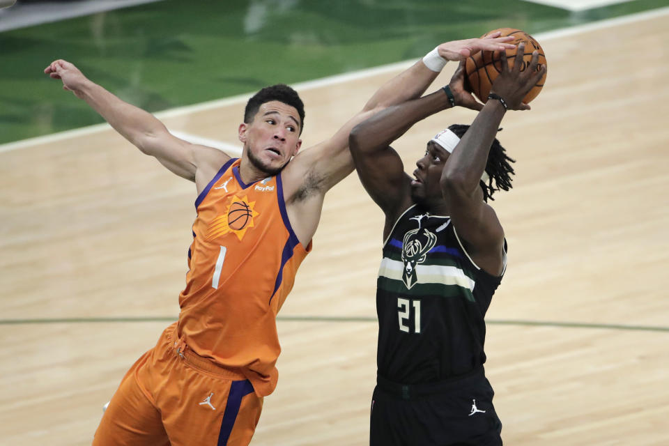 Milwaukee Bucks guard Jrue Holiday (21) is fouled by Phoenix Suns guard Devin Booker (1) during the second half of Game 6 of basketball's NBA Finals Tuesday, July 20, 2021, in Milwaukee. (AP Photo/Aaron Gash)