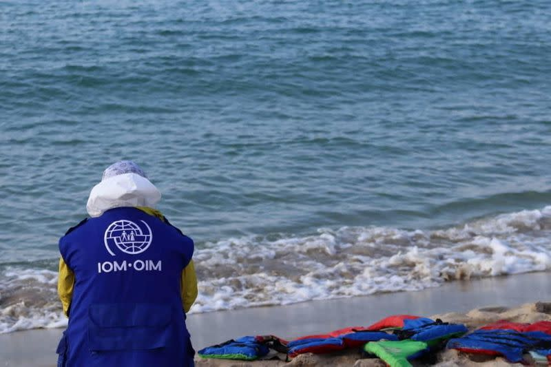 A handout image shows a member of International Organization for Migration sitting next to life jackets on the beach in Khums
