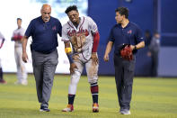 Atlanta Braves right fielder Ronald Acuna Jr., center, attempts to walk after trying to make a catch on an inside-the-park home run hit by Miami Marlins' Jazz Chisholm Jr. during the fifth inning of a baseball game, Saturday, July 10, 2021, in Miami. (AP Photo/Lynne Sladky)