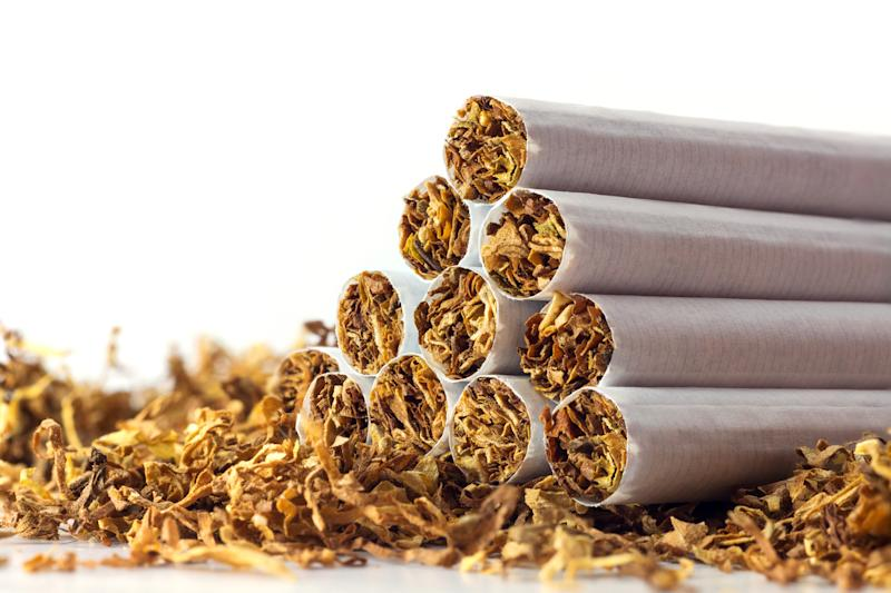 A pyramid of tobacco cigarettes laid atop a bed of dried tobacco.