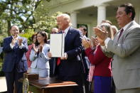 """President Donald Trump holds an executive order on the """"White House Hispanic Prosperity Initiative,"""" after signing it in the Rose Garden of the White House, Thursday, July 9, 2020, in Washington. (AP Photo/Evan Vucci)"""