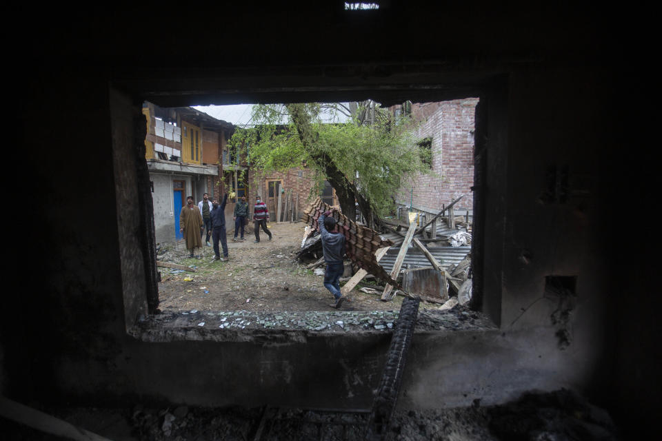 Kashmiri villagers inspect a house that was damaged during a gun battle between government forces and suspected rebels in Bijbehara, some 28 miles (45 kilometers) south of Srinagar, Indian controlled Kashmir, Sunday, April 11, 2021. (AP Photo/Mukhtar Khan)