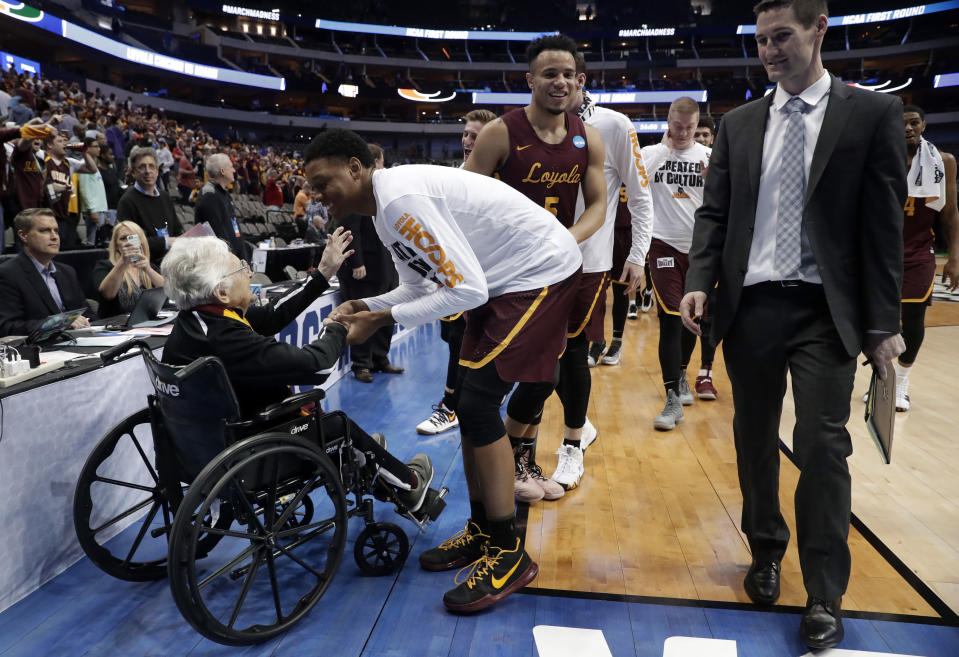 FILE - In this March 15, 2018, file photo, Sister Jean Dolores Schmidt, left, greets the Loyola Chicago basketball team as the Ramblers walk off the court after a win over Miami in a first-round game at the NCAA college basketball tournament in Dallas. Loyola Chicago is back in the tournament. And Sister Jean will be there, too. The 101-year-old team chaplain's lobbying paid off Tuesday, March 16, when the school reversed course and announced she will go. That means she gets to watch her beloved Ramblers in person for the first time this season when No. 17 Loyola meets Georgia Tech in Indianapolis on Friday. (AP Photo/Tony Gutierrez, File)