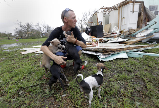<p>Sam Speights tries to hold back tears while holding his dogs and surveying the damage to his home in the wake of Hurricane Harvey, Aug. 27, 2017, in Rockport, Texas. (Photo: Eric Gay/AP) </p>