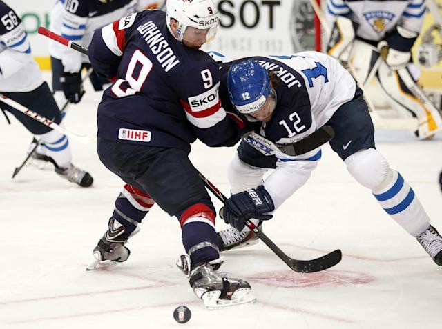 USA forward Tyler Johnson, left, battles for the puck with Finland forward Olli Jokinen during the Group B preliminary round match between USA and Finland at the Ice Hockey World Championship in Minsk, Belarus, Sunday, May 18, 2014. (AP Photo/Darko Bandic)