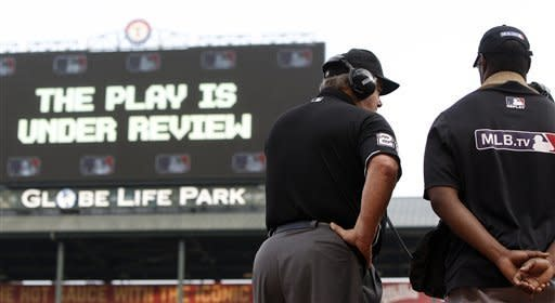 FILE - This May 16, 2015 file photo shows umpire Joe West (22) connecting with MLB's review command center in New York to review Texas Rangers left fielder Delino DeShields', not pictured, attempted sliding catch of a foul ball during the first inning of a baseball game against the Cleveland Indians in Arlington, Texas. Major League Baseball umpires could start explaining replay decisions to the players and fans _ the way NFL referees do _ later this season if the sides can reach agreement. Under one possible scenario, the crew chief could wear a microphone beginning at the All-Star Game. (AP Photo/Brandon Wade)