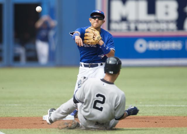 Toronto Blue Jays second baseman Munenori Kawasaki, top, turns a double play over New York Yankees' Derek Jeter during the first inning of a baseball game in Toronto, Sunday, Aug. 31, 2014. (AP Photo/The Canadian Press, Darren Calabrese)