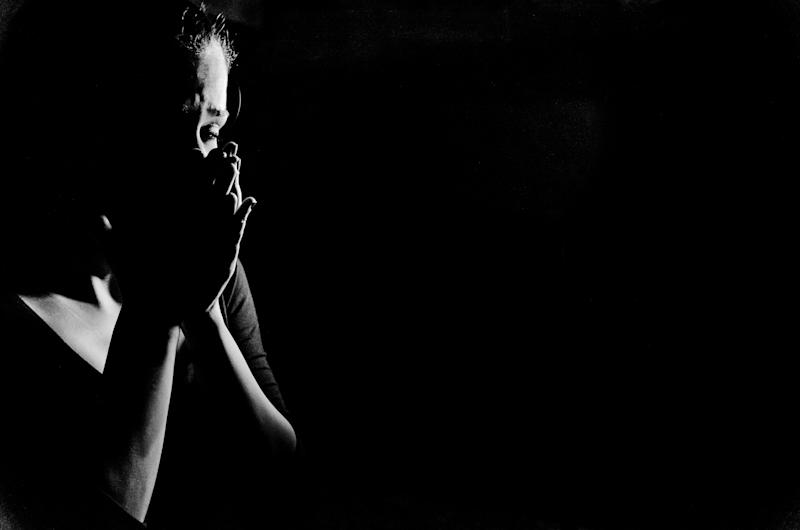 Young woman stanging in the dark crying,she is feeling hopless . (Photo: slkoceva via Getty Images)