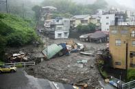 Houses are damaged by mudslide following heavy rain at Izusan district in Atami, west of Tokyo, Saturday, July 3, 2021. A powerful mudslide carrying a deluge of black water and debris crashed into rows of houses in a town west of Tokyo following heavy rains on Saturday, leaving multiple people missing, officials said. (Naoya Osato/Kyodo News via AP)