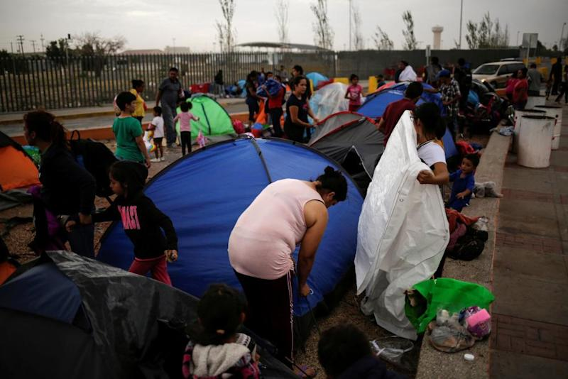 Mexicans camping near the Santa Fe international border crossing bridge while waiting to apply for asylum arrange their belongings as they are moved to a shelter due a storm forecast, in Ciudad Juárez, Mexico.