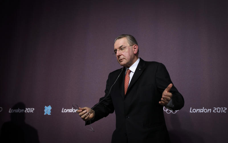 International Olympic Committee (IOC) President Jacques Rogges gestures to a reporter as he leaves after giving a press conference for the media at the 2012 Summer Olympics, Saturday, July 21, 2012, in London. (AP Photo/Ben Curtis)