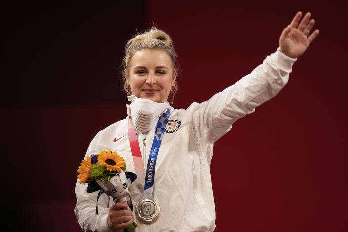 Katherine Elizabeth Nye of the United States waves after from the podium after receiving the silver medal for women's 76kg weightlifting, at the 2020 Summer Olympics, Sunday, Aug. 1, 2021, in Tokyo, Japan. (AP Photo/Luca Bruno)