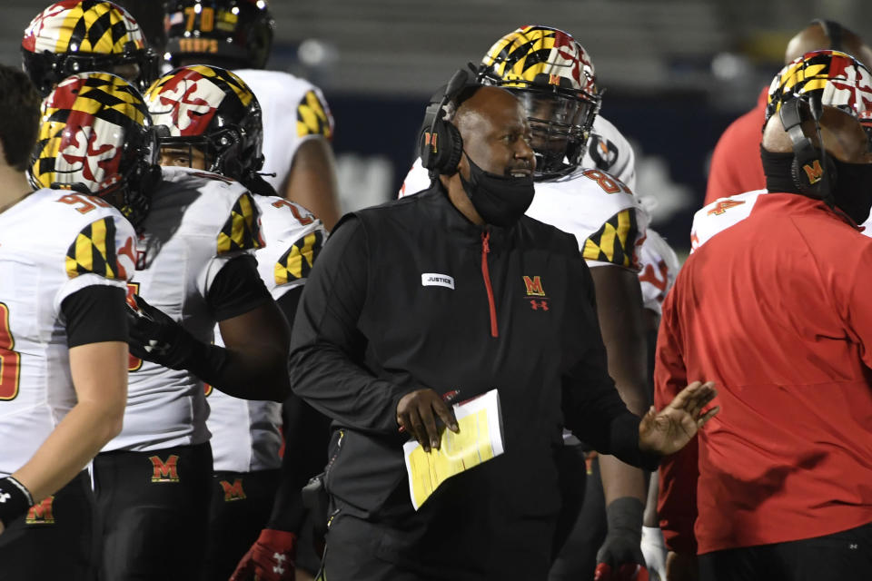 Maryland head coach Mike Locksley, center, talks with his players during a timeout late in the fourth quarter of an NCAA college football game in State College, Pa., Saturday, Nov. 7, 2020. (AP Photo/Barry Reeger)
