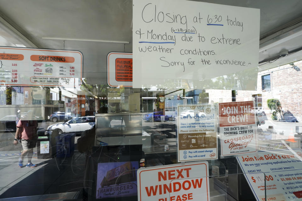 A sign in the window of the Dick's Drive-In in Seattle's Capitol Hill neighborhood is shown Monday, June 28, 2021, in Seattle. The walk- and drive-up restaurant, which is not air conditioned, closed early Sunday and all day Monday due to excessive heat. Seattle and other cities in the Pacific Northwest endured the hottest day of an unprecedented and dangerous heat wave on Monday, with temperatures obliterating records that had been set just the day before on Sunday. (AP Photo/Ted S. Warren)