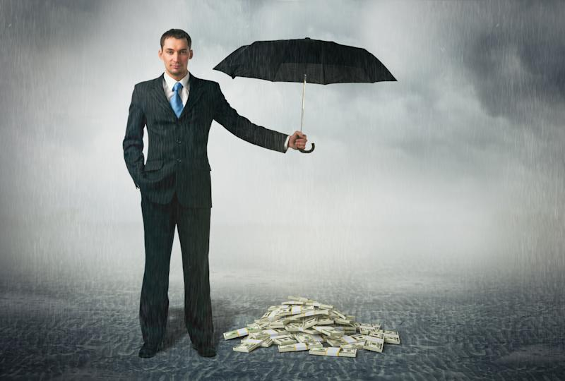 A man in a suit holds an umbrella over a pile of $100 bills.