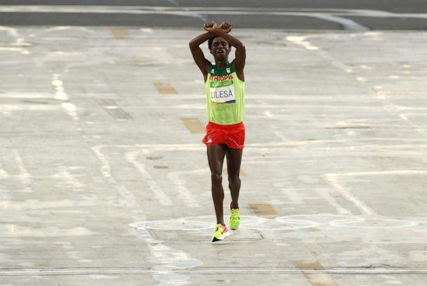 PHOTO: Feyisa Lilesa of Ethiopia crosses his arms as he crosses the finish line to win silver during the Men's Marathon on Day 16 of the Rio 2016 Olympic Games, August 21, 2016, in Rio de Janeiro. (Buda Mendes/Getty Images, FILE)