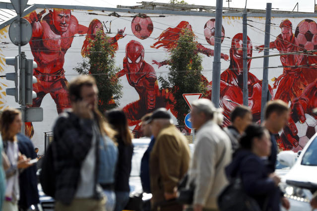 People cross the road passing by the graffiti of the Marvel Universe fictional characters playing with soccer balls in the background in Moscow, Russia, Thursday, June 14, 2018, ahead of the opening match of the 2018 soccer World Cup. (AP Photo/Pavel Golovkin)