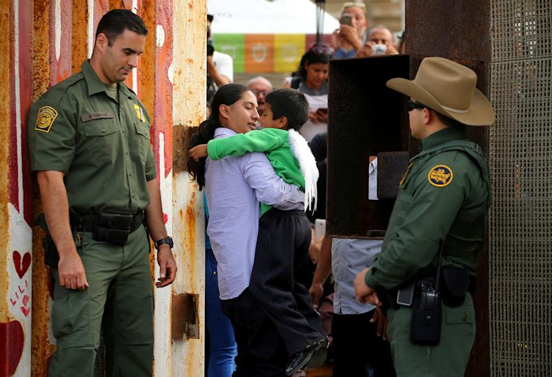 FILE PHOTO - U.S. Border patrol agents stand at an open gate on the fence along the Mexico border to allow Luis Eduardo Hernandez-Bautista hug Ty'Jahnae Williams and his father Eduardo Hernandez (not in view), as part of Universal Children's Day at the Border Field State Park, California, U.S. on November 19, 2016.  REUTERS/Mike Blake/File Photo