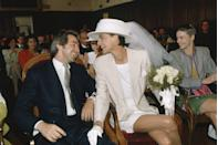 """<p>The always-chic Ines de la Fressange went for a new look for bridal fashion: The short dress. Yet, white gloves and a veil added a traditional touch to the ensemble.</p><p><a href=""""http://www.goodhousekeeping.com/beauty/fashion/g3868/wedding-dress-transformations/"""" rel=""""nofollow noopener"""" target=""""_blank"""" data-ylk=""""slk:9 incredible wedding dress transformations »"""" class=""""link rapid-noclick-resp""""><em>9 incredible wedding dress transformations »</em></a><br></p>"""