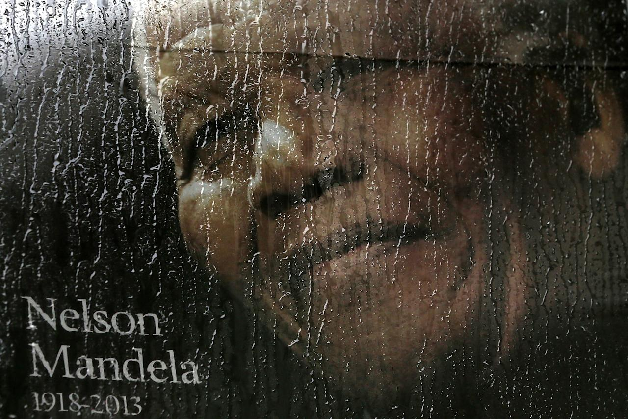 JOHANNESBURG, SOUTH AFRICA - DECEMBER 10: Rain falls on a poster of Nelson Mandela sitting in the window of a bus outside of Ellis Park before a telecast of the Nelson Mandela memorial service on December 10, 2013 in Johannesburg, South Africa. Over 60 heads of state have travelled to South Africa to attend a week of events commemorating the life of former South African President Nelson Mandela. Mr Mandela passed away on the evening of December 5, 2013 at his home in Houghton at the age of 95. Mandela became South Africa's first black president in 1994 after spending 27 years in jail for his activism against apartheid in a racially-divided South Africa. (Photo by Justin Sullivan/Getty Images)