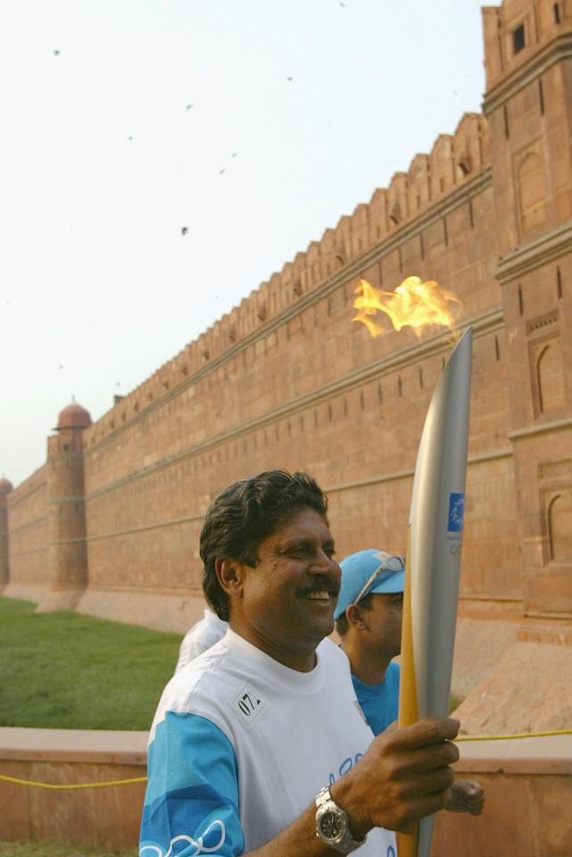 DELHI - JUNE 10: Torchbearer Kapil Dev carries the Olympic Flame outside the Red Fort during Day 7 of the ATHENS 2004 Olympic Torch Relay on June 10, 2004 in Delhi, India. The Olympic Flame travels to 34 cities in 27 countries en route to the Athens 2004 Olympic Games. (Photo by Todd Warshaw/Getty Images)