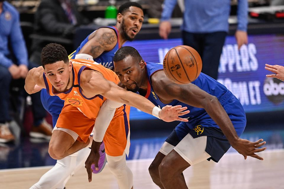 DENVER, CO - JUNE 11:  Devin Booker #1 of the Phoenix Suns is defended by Paul Millsap #4 of the Denver Nuggets in Game Three of the Western Conference second-round playoff series at Ball Arena on June 11, 2021 in Denver, Colorado. NOTE TO USER: User expressly acknowledges and agrees that, by downloading and or using this photograph, User is consenting to the terms and conditions of the Getty Images License Agreement. (Photo by Dustin Bradford/Getty Images)