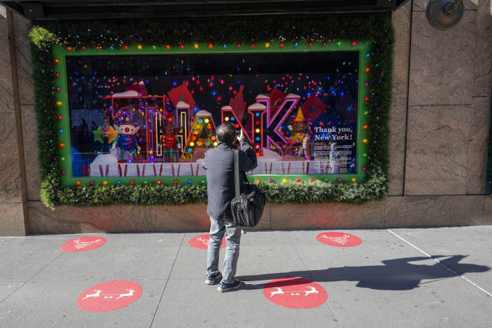 Red dots mark the spots for viewing the holiday windows display at the Macy's flagship as a man takes a photo, Friday, Nov. 20, 2020, in New York. Macy's 2020 holiday windows honors essential workers and first responders during the coronavirus pandemic. (AP Photo/Mary Altaffer)