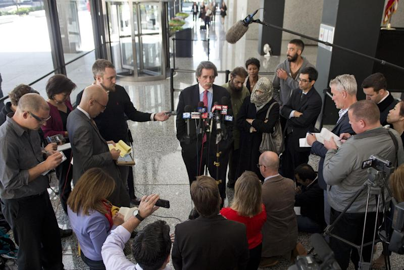 Zarine Kahn (R) and Shafi Ullah Khan (C), the parents of Mohammed Hamzah Khan, 19, listen as Thomas Anthony Durkin, the attorney for their son, talks to reporters after a bond hearing on October 9, 2014 in Chicago, Illinois