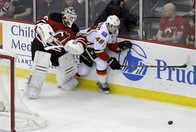 Calgary Flames' Bryce Van Brabant (48) skates after the puck away from New Jersey Devils goalie Cory Schneider (35) during the second period of an NHL hockey game in Newark, N.J., Monday, April 7, 2014. (AP Photo/Mel Evans)