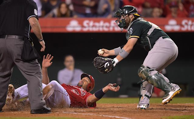Los Angeles Angels' Albert Pujols, center, slides into home after being tagged out by Oakland Athletics catcher Derek Norris while trying to score on a single by Josh Hamilton during the sixth inning of a baseball game, Tuesday, June 10, 2014, in Anaheim, Calif. (AP Photo/Mark J. Terrill)