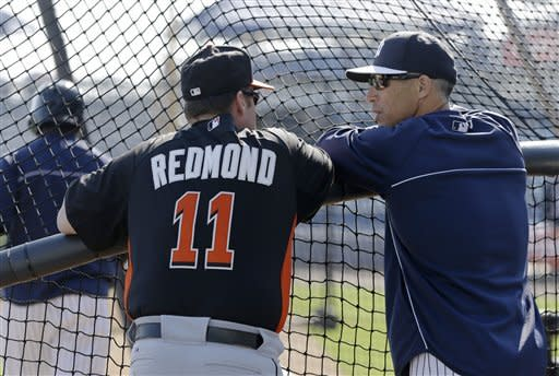 Miami Marlins manager Mike Redmond (11) talks with New York Yankees manager Joe Girardi behind the batting cage before a spring training baseball game between their two teams in Tampa, Fla., Friday, March 15, 2013. (AP Photo/Kathy Willens)