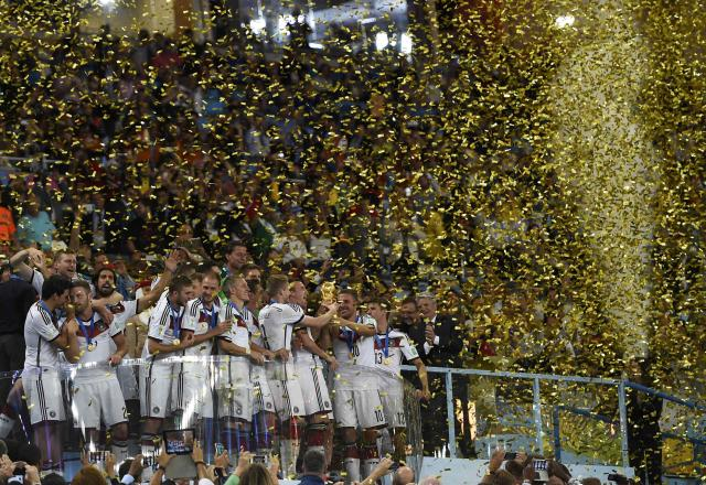 Germany's soccer players celebrate with the World Cup trophy after the 2014 World Cup final between Germany and Argentina at the Maracana stadium in Rio de Janeiro July 13, 2014. REUTERS/Dylan Martinez (BRAZIL - Tags: SOCCER SPORT WORLD CUP)